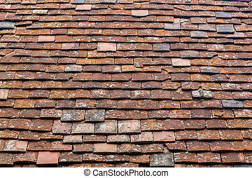 Old Tiles on a Roof Background - A closeup to old tiles on a...