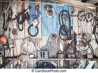 old tools hanging on wooden wall