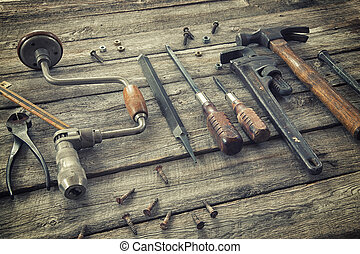 Old tools on rough wood surface - Old antique tools on a ...