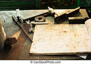 Old tools on workplace of turner with chart