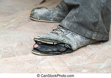 Old torn boots on the man's feet
