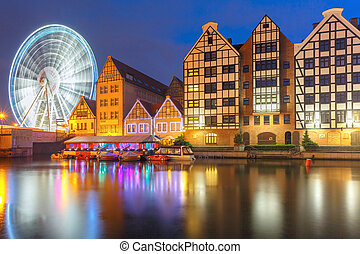 Ferris wheel with water reflection at Trade fair St Dominic in Old Town of Gdansk at night, Poland