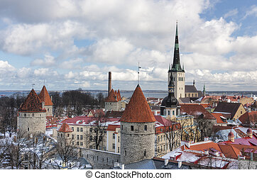 historic Old Town of Tallinn, capital of Estonia. Roofs are covered with snow. Church St. Olaf (Oleviste) at background, curtain wall with towers in foreground.