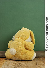 Old toy bunny on a wooden floor