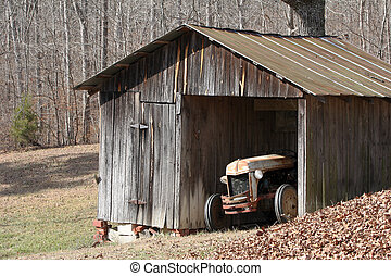 Old tractor in shed - An old tractor in a shed with pasture...