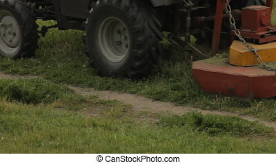 Old tractor mows the grass on the field, farmer, close-up