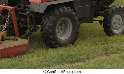 Old tractor mows the grass on the field, farmer