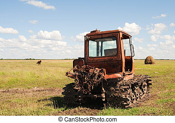 Old tractor on the meadow at hay-making time