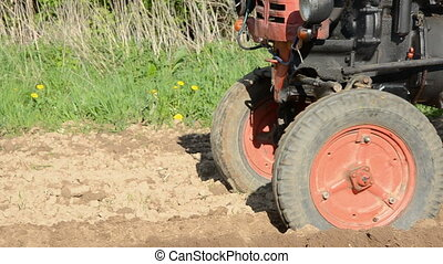 old tractor planting potatoes
