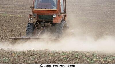 Old tractor plowing field. Farmer plowing the field,...