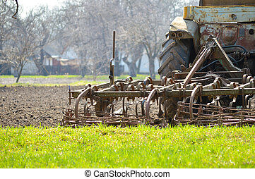 Old tractor plowing field on spring day