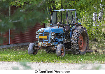 Old tractor with chains on the wheels standing under a tree