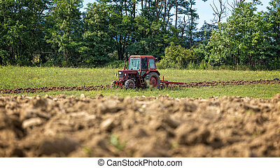 Old tractor working on the field