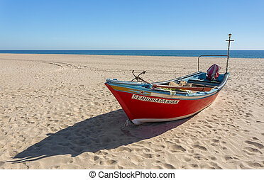 Old traditional fishing boat on the beach. In Portugal.