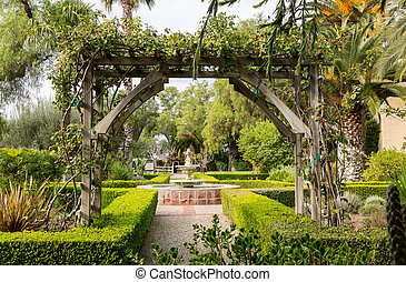 Old traditional garden with pathways and fountain -...