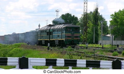 Old train goes through the railway crossing, smokes. - The...