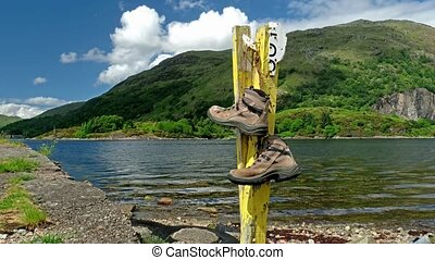 Old tramping boots hanging on a post close to ocean - time...