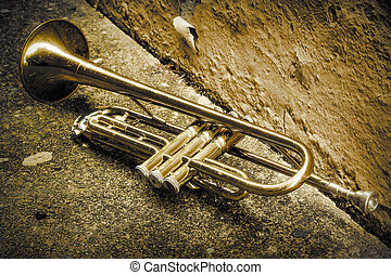 Old worn trumpet stands alone in alleyway behind a jazz club