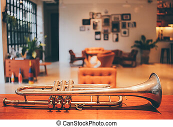 Old trumpet in vintage living room with retro filter effect