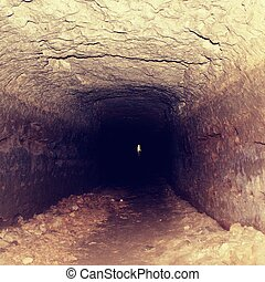 Old tunnel, moistened walls. Dry channel carved in sandstone rock