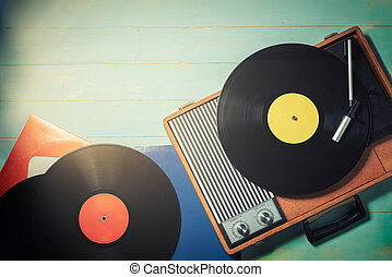 Old turntable with a vinyl records on rustic wooden table
