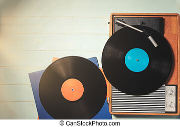 Old turntable with a vinyl records on wooden table