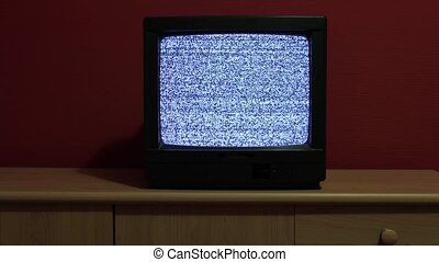 No signal just noise on an old TV set in room with red wall