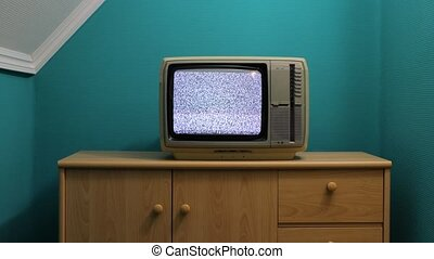 Old tube TV set with white noise in room with green wall, loopable