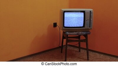 Vintage TV set on a chair in an empty room, copy space
