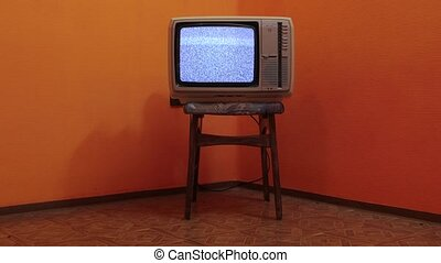 Old TV no signal - Vintage TV set on a chair in an empty...