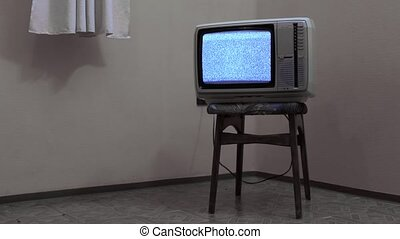 Vintage TV set on a chair in an empty room