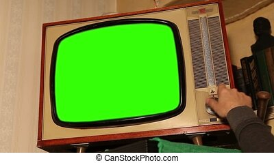 Old TV with green screen, retro TV in an old interior with a green screen