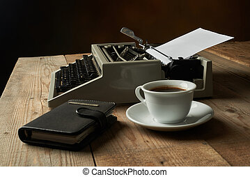 Old typewriter on wooden table with blank paper