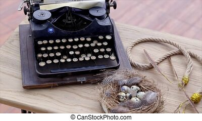 Old typewriter vintage ornaments and nest on a wooden table