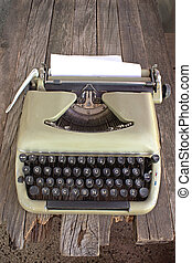 Old typewriter with blank paper on wooden background