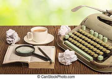 Old typewriter with paper on green bright blur background