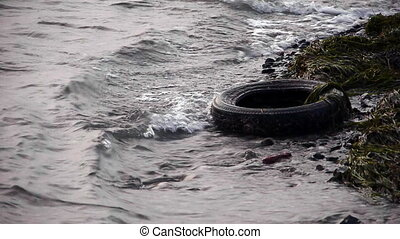 Old tyre in dirty polluted sea - Hazardous - Environment -...