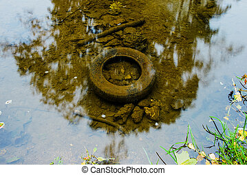 old tyre in the water, ecology concept