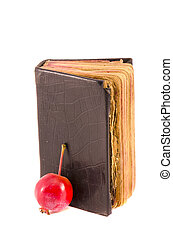old used christianity prayer book Bible with red apple isolated on white background