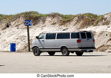 Old van driving on the beach, southern Texas, USA