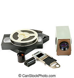 Old videocassettes and video projector with slides isolated on white background.
