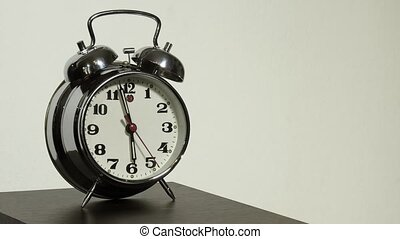 Old vintage alarm clock on a table, white background