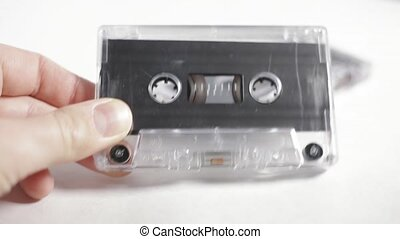 Old vintage audio cassette on a white background in male's hand.