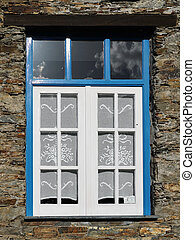 Old vintage blue window with blue trim and a rustic stone wall
