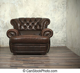 Old vintage brown leather chair in empty room