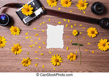 Old vintage camera lying on the wooden background. Film and three lenses lie on a table. Place for design. Blank white sheet of paper. Yellow flowers and petals. A flower with a green stem.