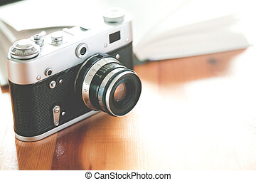 Old vintage camera with book on a wooden table.