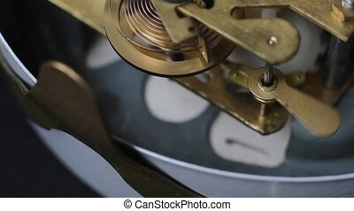 Old vintage clock mechanism working, closeup shot with soft focus. Close up of a internal clock mechanism. Vintage Watch Gears Movement Macro.
