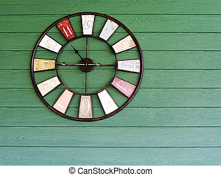 Old vintage clock on green wooden plank wall background.