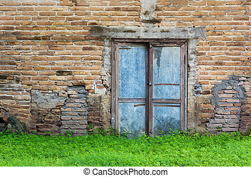 Old Vintage Door On The Old Brick Wall And Green Grass.